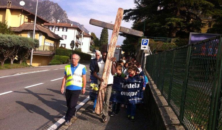 Bambini e richiedenti camminano insieme alla Croce di Lampedusa.