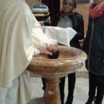 Don Alberto bagna nella fonte battesimale Rebecca.